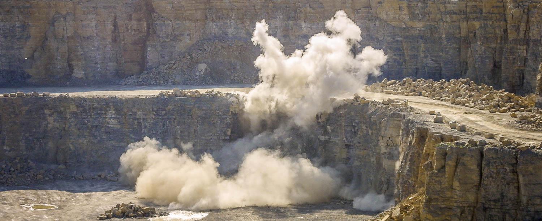 Produktionsablauf - Sprengen - die Sprengung mit ihrer Staubwolke